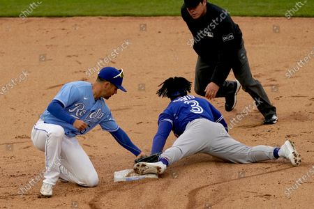 Toronto Blue Jays' Jonathan Davis (3) beats the tag by Kansas City Royals second baseman Whit Merrifield to steal second during the seventh inning in the first baseball game of a doubleheader, in Kansas City, Mo. The Blue Jays won 5-1