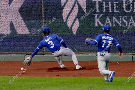 Toronto Blue Jays center fielder Jonathan Davis (3) and right fielder Josh Palacios (77) try to corral an RBI double hit by Kansas City Royals' Carlos Santana during the third inning in the second baseball game of a doubleheader, in Kansas City, Mo