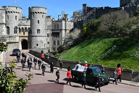 Britain's Prince Charles, from front left, Princess Anne, Prince Andrew. Prince Edward, Prince William, Peter Phillips, Prince Harry, Earl of Snowdon, Tim Laurence and Queen Elizabeth II, in car at rear, follow the coffin as it makes it's way past the Round Tower during the funeral of Britain's Prince Philip inside Windsor Castle in Windsor, England