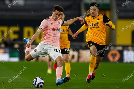 Sheffield United's Ethan Ampadu, left, is challenged by Wolverhampton Wanderers' Ki-Jana Hoever during the English Premier League soccer match between Wolves and Sheffield United at the Molineux Stadium in Wolverhampton, England