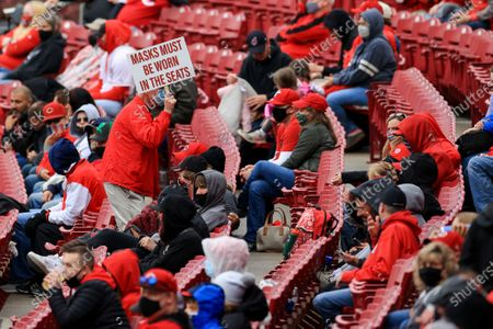 An usher carries a sign reminding fans to wear a mask during the second inning of a baseball game between the Cleveland Indians and the Cincinnati Reds in Cincinnati