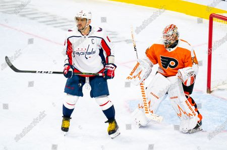 Washington Capitals' Alex Ovechkin, left, looks for the puck while in front of Philadelphia Flyers' Alex Lyon, right, during the third period of an NHL hockey game, in Philadelphia. The Capitals won 6-3