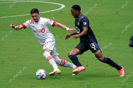 Toronto FC midfielder Marco Delgado (8) and CF Montreal forward Mason Toye (13) go for the ball during the first half of an MLS soccer match, in Fort Lauderdale, Fla