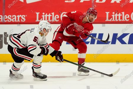 Stock Picture of Detroit Red Wings left wing Darren Helm (43) shoots the puck as Chicago Blackhawks defenseman Ian Mitchell (51) defends during the second period of an NHL hockey game, in Detroit
