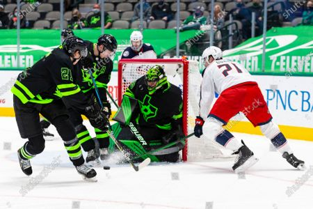 Dallas Stars goaltender Jake Oettinger (29) blocks a shot from Columbus Blue Jackets center Joshua Dunne during the third period of an NHL hockey game, in Dallas