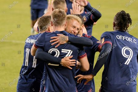 Stock Picture of Chicago Fire defender Francisco Calvo (5) hugs forward Robert Beric (27) in celebration of Beric's goal against the New England Revolution during the first half of an MLS soccer match in Chicago