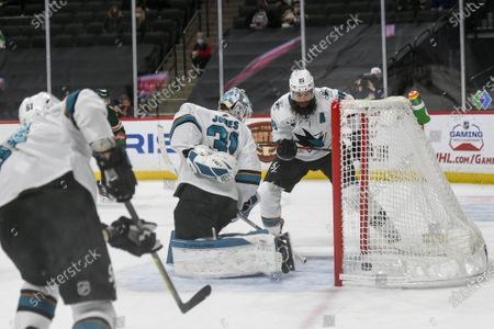 Stock Photo of San Jose Sharks goalie Martin Jones, center, and defenseman Brent Burns, right, turn to watch the puck go into the goal after a shot by Minnesota Wild right wing Mats Zuccarello during the first period of an NHL hockey game, in St. Paul, Minn