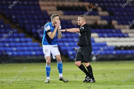 Mark Beevers of Peterborough United reacts as match official Lee Swabey points to the penalty spot during the Sky Bet League 1 match between Peterborough and Northampton Town at Weston Homes Stadium, Peterborough, England on 16th April 2021.