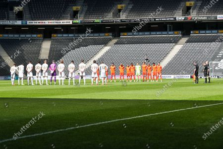 Players and officials pay respect to Prince Phillip before the Sky Bet League One match between MK Dons and Portsmouth at Stadium MK, Milton Keynes, England on 17th April 2021.