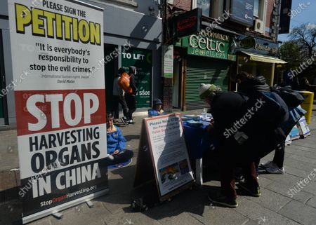 Stock Image of Falun Gong practitioners attend a protest on Grafton Street in Dublin city center, during the COVID-19 lockdown. Falun Gong is a spiritual discipline which spread in China during the 90's. Its practice was progressively opposed by Chinese government. Right human associations allege abuses, tortures, illegal imprisonments, forced labors and murder of Falun Gong followers and organ harvesting to supply transplant industry. On Saturday, 17 April 2021, in Dublin, Ireland.