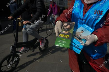 Stock Photo of Falun Gong practitioner attend a protest on Grafton Street in Dublin city center, during the COVID-19 lockdown. Falun Gong is a spiritual discipline which spread in China during the 90's. Its practice was progressively opposed by Chinese government. Right human associations allege abuses, tortures, illegal imprisonments, forced labors and murder of Falun Gong followers and organ harvesting to supply transplant industry. On Saturday, 17 April 2021, in Dublin, Ireland.