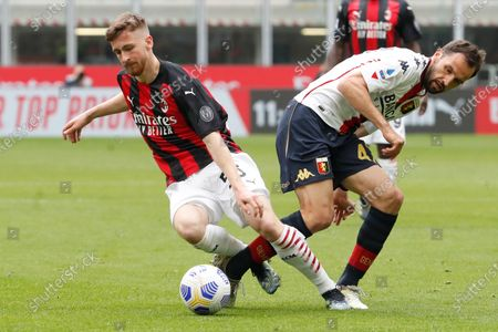 Milan's Alexis Saelemaekers, left, is challenged by Genoa's Milan Badelj during the Serie A soccer match between AC Milan and Genoa at the San Siro stadium in Milan, Italy