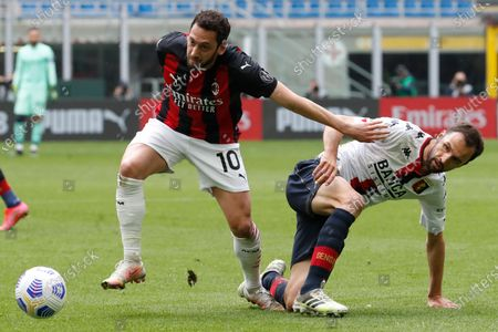 Milan's Hakan Calhanoglu, left, is challenged by Genoa's Milan Badelj during the Serie A soccer match between AC Milan and Genoa at the San Siro stadium in Milan, Italy