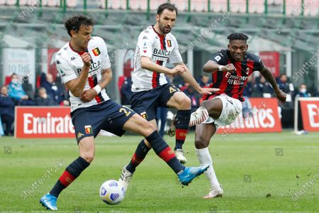 Milan's Rafael Leao, right, is challenged by Genoa's Ivan Radovanovic, left and Genoa's Milan Badelj during the Serie A soccer match between AC Milan and Genoa at the San Siro stadium in Milan, Italy