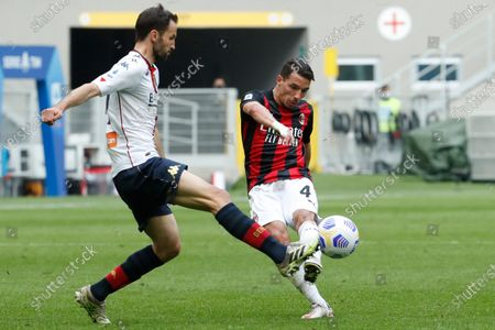 Milan's Ismael Bennacer, right, is challenged by Genoa's Milan Badelj during the Serie A soccer match between AC Milan and Genoa at the San Siro stadium in Milan, Italy