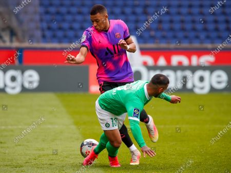 PSG's Kylian Mbappe, left, and Saint-Etienne's Miguel Trauco battle for the ball during the French League One soccer match between Paris Saint-Germain and St Etienne at Parc Des Princes in Paris, France