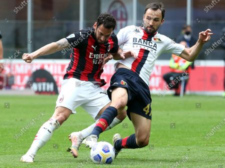 AC Milan's Hakan Calhanoglu (L) challenges for the ball  Genoa's Milan Badelj during the Italian serie A soccer match between AC Milan and Genoa CFC at Giuseppe Meazza stadium in Milan, Italy, 18  April 2021.