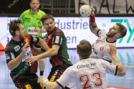 Domagoj Pavlovic (right) of MT Melsungen is attacked by Christian O'Sullivan (left) and Marko Bezjak (middle) of Magdeburg during the LIQUI MOLY Handball-Bundesliga match between SC Magdeburg and MT Melsungen at GETEC-Arena on April 18, 2021 in Magdeburg, Germany.