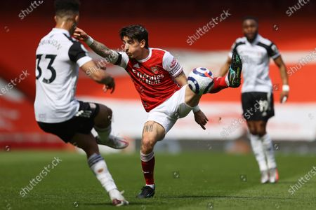 Arsenal's Hector Bellerin, centre, challenges for the ball with Fulham's Antonee Robinson, left, during an English Premier League soccer match between Arsenal and Fulham at the Emirates stadium in London, England