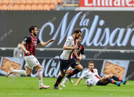 Milan Badelj of Genoa CFC fights for the ball against Hakan Calhanoglu of AC Milan