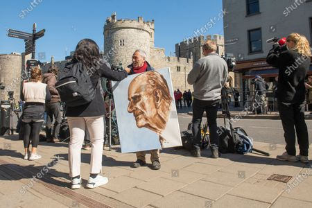 After seven days of mourning Prince Philip will be laid to rest today (Sat) in a small private funeral at St George's Chapel, Windsor, Berks..Picture showsArtist Kaya Mar holds a portrait he has painted of the Duke of Edinburgh outside Windsor Castle.