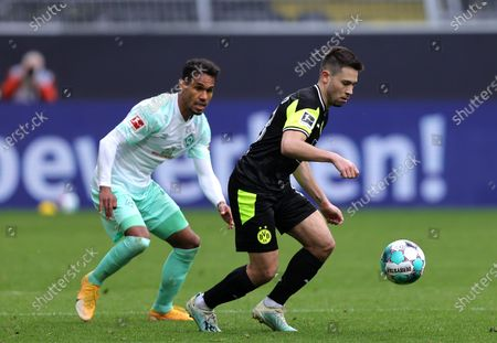 Raphael Guerreiro (R) of Dortmund in action against Theodor Gebre Selassie (L) of Bremen during the German Bundesliga soccer match between Borussia Dortmund and Werder Bremen in Dortmund, Germany, 18 April 2021.