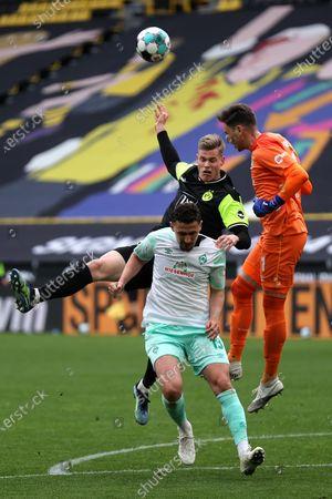 Steffen Tigges (C) of Dortmund in action against Bremen's goalkeeper Jiri Pavlenka (R) and Milos Veljkovic (front) during the German Bundesliga soccer match between Borussia Dortmund and Werder Bremen in Dortmund, Germany, 18 April 2021.