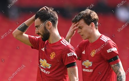 Manchester United's Bruno Fernandes, left, and Manchester United's Victor Lindelof react during the English Premier League soccer match between Manchester United and Burnley at the Old Trafford stadium in Manchester, England