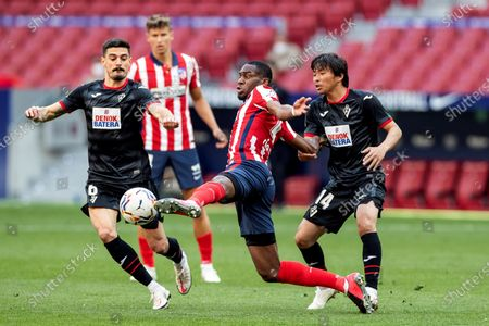 Atletico Madrid's midfielder Geoffrey Kondogbia (C) vies for the ball with Eibar's midfielders Aleix Garcia (L) and Takashi Inui (R) during the Spanish LaLiga soccer match between Atletico Madrid and SD Eibar held at Wanda Metropolitano stadium in Madrid, central Spain, 18 April 2021.
