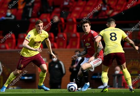 Manchester United's Victor Lindelof (C) in action against Burnley players Chris Wood (L) and Josh Brownhill (R) during the English Premier League soccer match between Manchester United and Burnley FC in Manchester, Britain, 18 April 2021.
