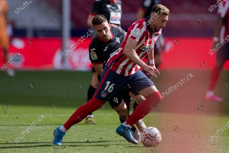 Atletico Madrid's Hector Herrera, foreground, duels for the ball with Eibar's Kevin Rodrigues during the Spanish La Liga soccer match between Atletico Madrid and Eibar at Wanda Metropolitano stadium in Madrid, Spain