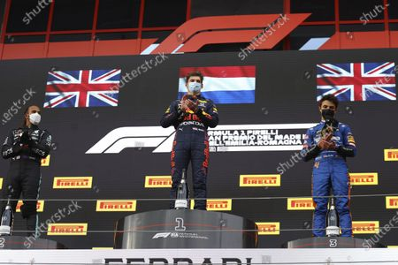 Stock Image of From left, second placed Mercedes Lewis Hamilton, first placed Red Bull's Max Verstappen and third placed McLaren's Lando Norris celebrate on the podium at the end of the Emilia Romagna Formula One Grand Prix, at the Imola racetrack, Italy