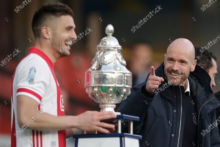 Ajax's head coach Erik ten Hag, right, gestures as captain Dusan Tadic is about to lift the trophy after winning the TOTO KNVB Cup final soccer match between Ajax and Vitesse at De Kuip stadium in Rotterdam, Netherlands