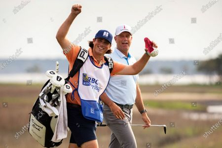 Reagan Cink raises his arms to the crowd while walking with his father Stewart Cink up the 18th fairway to the green during the final round of the RBC Heritage golf tournament in Hilton Head Island, S.C