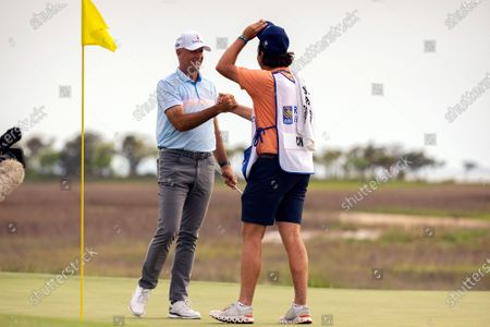 Stewart Cink, left, and his caddie and son Reagan Cink celebrate after sinking the winning putt on the 18th green during the final round of the RBC Heritage golf tournament in Hilton Head Island, S.C