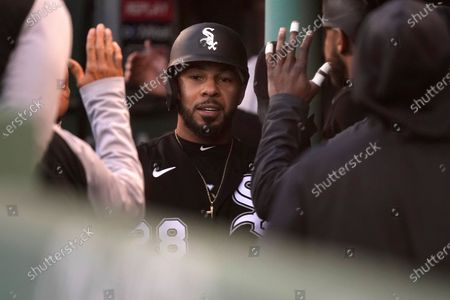 Chicago White Sox's Leury Garcia, center, is welcomed into the dugout after scoring on a sacrifice fly by Nick Madrigal in the sixth inning of a baseball game against the Boston Red Sox, in Boston. The game is the second of a doubleheader Sunday