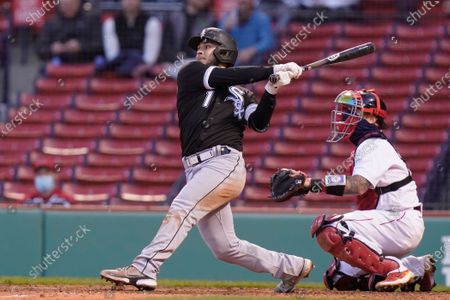 Chicago White Sox's Nick Madrigal, left, hits a sacrifice fly, allowing teammate Leury Garcia to score, as Boston Red Sox's Christian Vazquez, right, looks on in the sixth inning of a baseball game, in Boston. The game is the second of a doubleheader Sunday