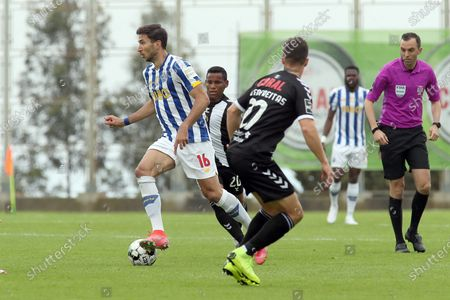 Nacional player Ruben Freitas (C) fights for the ball with Marko Grujic (L) of FC Porto during their Portuguese First League soccer match held at Madeira Stadium, in Funchal, Madeira Island, Portugal, 18 April 2021.