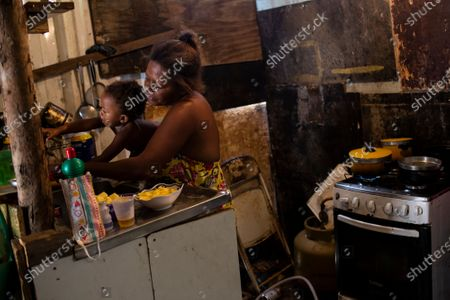 Stock Photo of Debora Estanislau, who before the new coronavirus pandemic hit made her living as a domestic worker holds her one-year-old daughter Ana Beatriz as she cooks at home where she lives with her four children at the Cidade de Deus favela, in Rio de Janeiro, Brazil