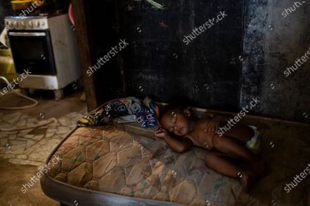 Ana Beatriz sleeps on a mattress while her mother Debora Estanislau, who before the new coronavirus pandemic hit made a living as a domestic worker cooks, in the house where she lives with her four children at the Cidade de Deus favela, in Rio de Janeiro, Brazil