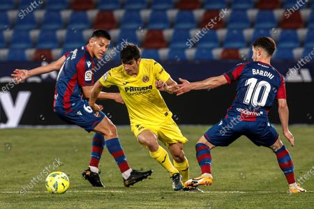 Villarreal's striker Gerard Moreno (C) vies for the ball with Levante's midfielder Enis Bardhi (R) and defender Oscar Duarte (L) during the Spanish LaLiga soccer match between Villarreal CF and Levante UD held at Ciutat de Valencia stadium, in Valencia, eastern Spain, 18 April 2021.