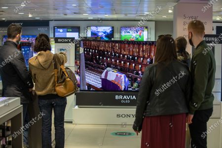 UKPicture shows a number of customers in the television department (one lady even bringing her own chair) at John Lewis on Oxford Street watching Prince Philip, Duke of Edinburgh funeral screened live television, London, UK