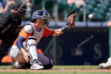 Houston Astros catcher Jason Castro, second from left, catches during the first inning of a baseball game against the Seattle Mariners as home plate umpire Brian O'Nora, left, looks, in Seattle