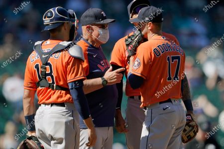 Houston Astros starting pitcher Jake Odorizzi (17) talks with pitching coach Brent Strom, second from left, and catcher catcher Jason Castro during a mound conference in the fifth inning of a baseball game against the Seattle Mariners, in Seattle