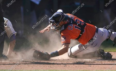 Houston Astros catcher Jason Castro dives in a cloud of dust but cannot get to Seattle Mariners' Tom Murphy who slides safely home on an RBI-double hit by Mitch Haniger during the seventh inning of a baseball game, in Seattle
