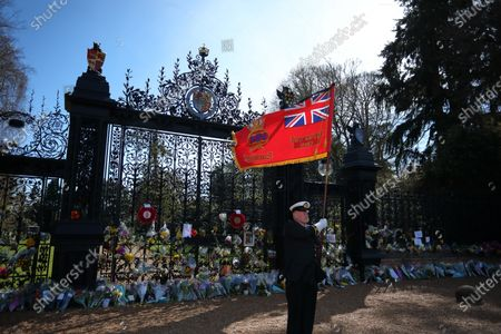 John Houston, formerly of the Merchant Navy, and now flag bearer for the local British Legion, pays his respects outside The Norwich Gates.Sandringham is very sombre on the day of the funeral of Prince Philip, Duke of Edinburgh. People have laid floral tributes outside The Norwich Gates, at Sandringham House, Norfolk, which is the winter retreat of Queen Elizabeth II. Prince Philip has spent much of his time in the Sandringham area since his retirement in 2017.