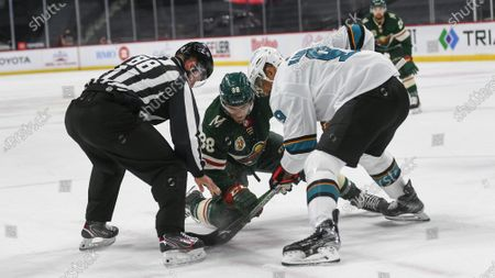 Minnesota Wild right wing Ryan Hartman, center, faces off against San Jose Sharks left wing Evander Kane during the first period of an NHL hockey game, in St. Paul, Minn. The Wild won 5-2