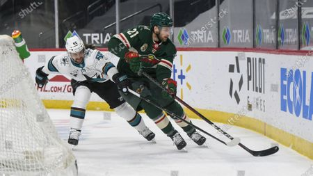San Jose Sharks defenseman Erik Karlsson, left, and Minnesota Wild defenseman Carson Soucy battle for the puck during the first period of an NHL hockey game, in St. Paul, Minn. The Wild won 5-2