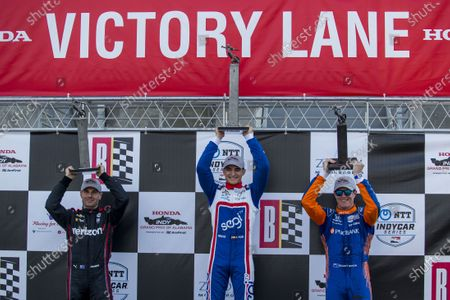 Team Penske driver Will Power, from left, (second place), Chip Ganassi Racing driver Alex Palou (first place), and Team Penske driver Scott McLaughlin (third place) hoist their trophies following the Honda Indy Grand Prix of Alabama auto race at Barber Motorsports Parkway, in Birmingham, Ala