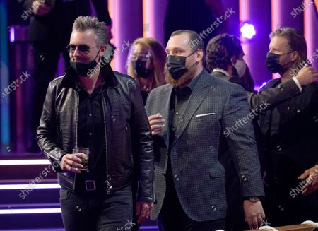 Eric Church, left, and Luke Combs appear at the 56th annual Academy of Country Music Awards, at the Grand Ole Opry in Nashville, Tenn. In background right is Thomas Rhett